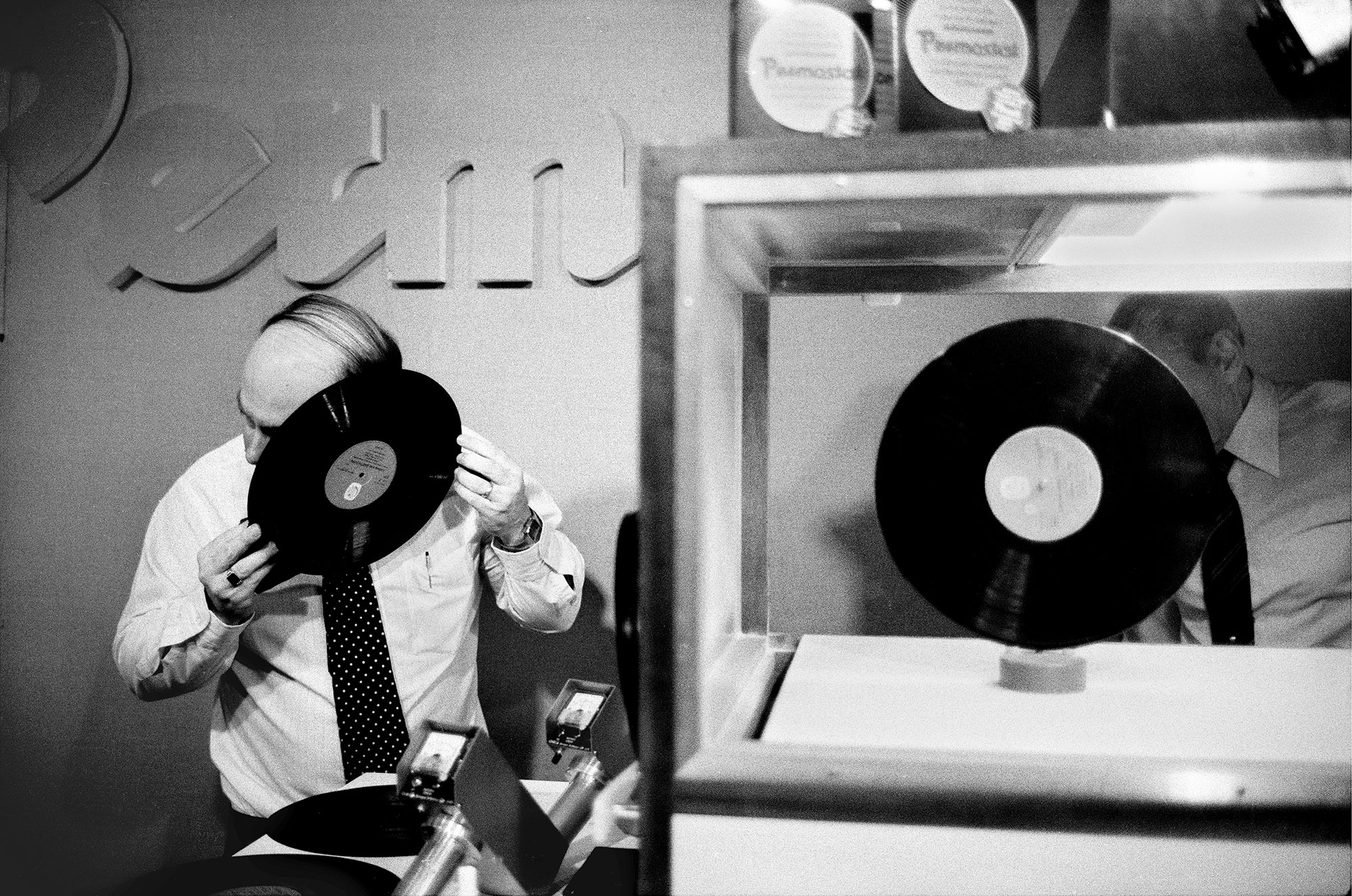 Photo horizontale en noir et blanc de Guy Le Querrec – Magnum Photos Un disque vinyl trône dans une vitrine d'exposition. À côté, un homme dégarni en chemise et cravate colle son oreille contre la galette d'un autre vinyl.