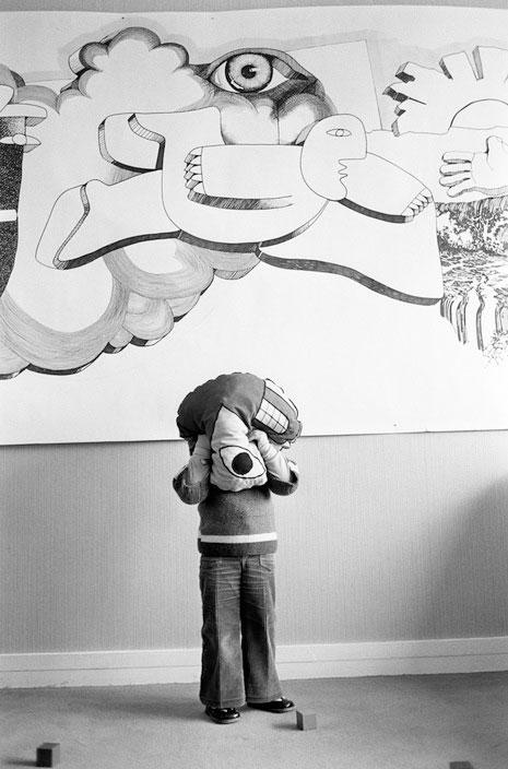 Photo verticale en noir et blanc de Jean Gaumy – Magnum Photos Un enfant en pantalon pattes d'eph' est debout devant un mur blanc. Il se cache le visage dans un coussin décoré d'une bouche et d'un œil. En haut du mur, une grande fresque peinte représente naïvement un homme qui vole dans les nuages, surplombé par un gros œil.