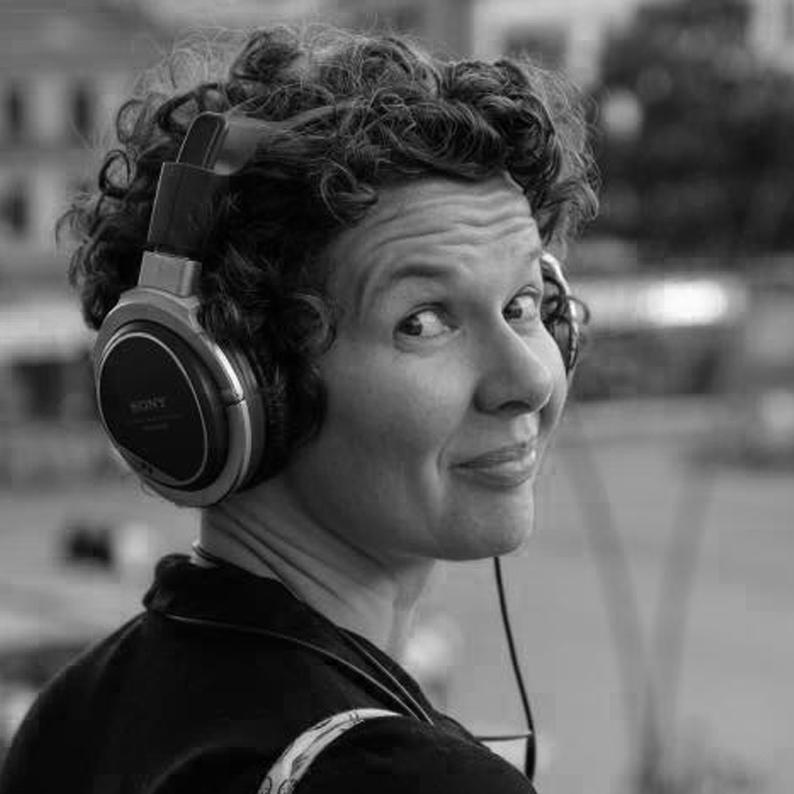 Séverine SKIERSKI - Audiodescriptrice - artisan de l'accessibilité sur des missions ponctuelles. De dos, Séverine Skierski lance un regard espiègle par-dessus son épaule. Ses cheveux sont courts et bouclés. Elle a une quarantaine d'années et un gros casque audio sur les oreilles.