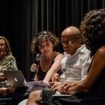 Sur la scène, Marie Gaumy, micro à la main et ordinateur sur les genoux pointe en souriant les feuilles de notes d'Emerson Silva, le traducteur.