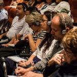 Dans la salle, le public prend des notes, un casque sur les oreilles.