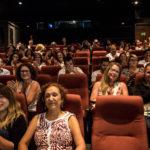 Installés dans les fauteuils rouges de la salle de cinéma, une petite centaine de personnes applaudit en souriant.