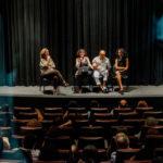 Devant le rideau bleu sombre d'une salle de cinéma, Marie Gaumy, Liliana Tavares (directrice de COM Acessibilidade Comunicacional, Recife), Livia Motta (directrice de Ver com Palavras, Sao Paulo) animent un débat traduit par Emerson Silva.