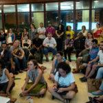 Debouts, assis sur des chaises, des canapés ou par terre, une trentaine de personnes valides et handicapées visuelles écoutent attentivement.