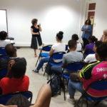 Dans une salle toute blanche, Marie Gaumy, en jupe noire et blanche, parle debout face à une vingtaine d'étudiants aux habits colorés et installés sur des chaises bleues.