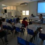 Dans la pénombre d'une salle de conférence, des lycéens sont assis devant un écran de cinéma allumé. Marie Gaumy est assise sous l'écran et anime l'atelier.