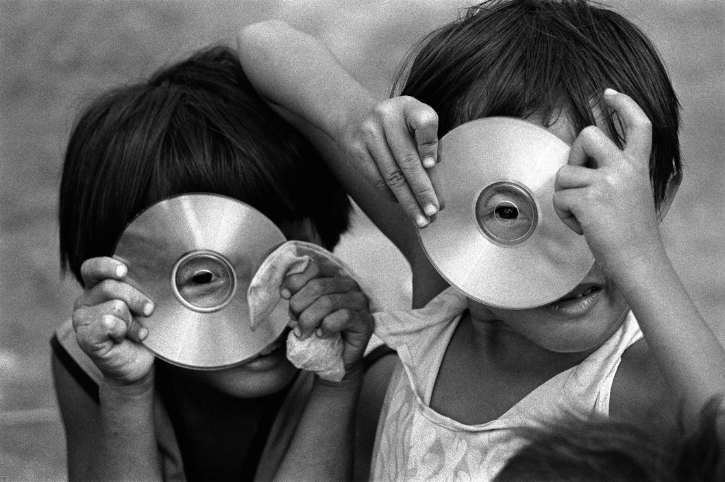 Photo horizontale en noir et blanc de Philip Jones Griffiths. Magnum Photos Deux petites filles asiatiques aux cheveux courts dissimulent chacune leur visage derrière la galette argentée d'un CD. Elles nous observent, l'œil collé contre le trou central de leur disque.