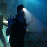Photo horizontale en couleur de Nicolas Petisoff pour le spectacle : « La révérence » de Hala Goshn Dans une lumière aquatique bleue et verte, deux silhouettes avancent, les mains levées, doigts écartés, un masque à hublot et petit projecteur sur la tête.