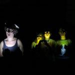 Photo couleur horizontale du spectacle : « La révérence » de Hala Goshn. Quatre personnages sont plongés dans le noir et s'éclairent par en dessous à la lumière de leur portable. L'un d'eux, éclairé de blanc, porte un marcel noir et une casquette de capitaine. Les trois autres sont groupés derrière lui, nimbés d'une lumière jaune. Leurs visages spectraux sont creusés d'ombres.