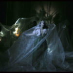 Photo horizontale en couleur de Pascal Victor pour le spectacle : « La traviata, vous méritez un avenir meilleur » de Benjamin Lazar, Florent Hubert et Judith Chemla. Dans la pénombre, une femme en robe de soirée verte cherche son souffle, prisonnière d'un immense voile de tulle blanc qu'elle tente d'éloigner en écartant les bras.