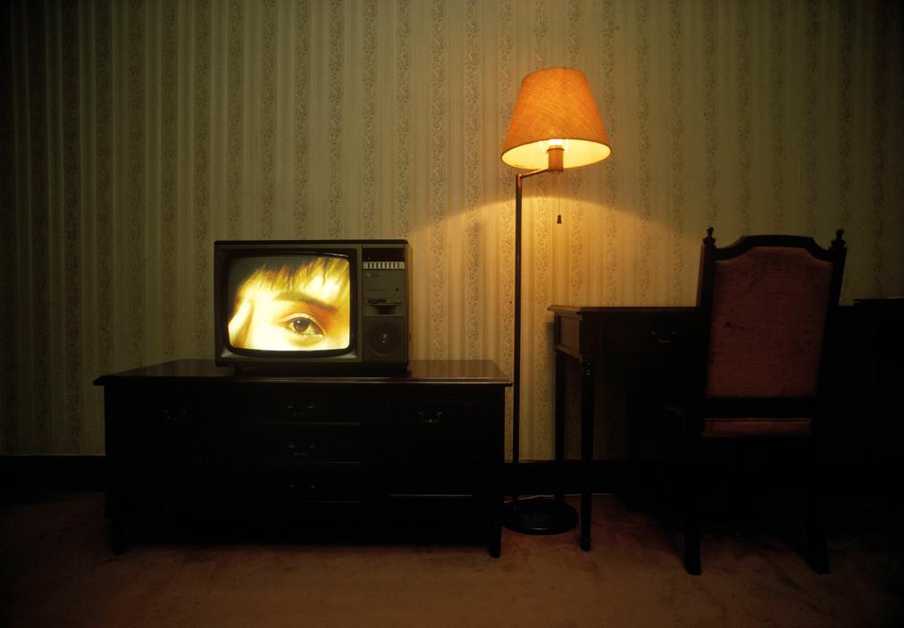 Photo horizontale en couleur de René Burri – Magnum Photos. Un œil nous fixe sur l'écran d'un gros poste de télévision allumé. Le poste repose sur un meuble bas et sombre. À côté, un bureau en bois laqués tout aussi sombre. Entre deux, une lampe à pied et son abat-jour ocre éclaire faiblement le papier peint vieillot d'une chambre moquettée de marron.