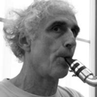 François LEBEGUE - Président de l'association Les Yeux Dits - Directeur de l'école de musique l'AMH. François Lebègue a une soixantaine d'années, les sourcils noirs et les cheveux blancs bouclés. Il souffle dans un embout de clarinette, le regard dense et concentré.