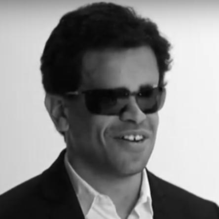 Salim EJNAÏNI - Auteur, kinésithérapeute et cavalier de sauts d'obstacle handisport - Consultant et membre d'honneur de l'association Les Yeux Dits. À peine 30 ans. Cheveux noirs, lunettes noires, veste noire sur chemise blanche. Sourire éclatant.